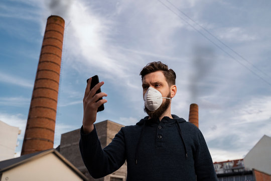 Man with his anti pollution mask on checking air quality , smoke from factory in the back