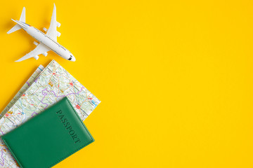 Summer travel concept. Flat lay traveler accessories on yellow background with copy space. Top view plane, passport, map. Travel agency banner design template