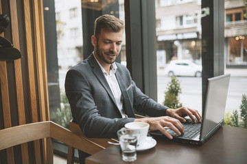 Business manager drinking coffee and using laptop