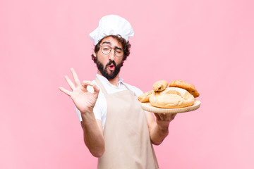 young crazy baker man holding bread against pink wall
