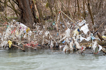 Polluted river. Plastic bags, bottles, garbage and trash dumped in the river in nature. Rubbish and waste floating in contaminated river. Ecological and environmental disaster. Ecology issue. Garbage.