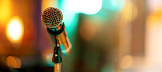 Close up of high fidelity microphone setting on stand with colorful abstract light bokeh background in conference seminar hall . Microphone on stage banner size.