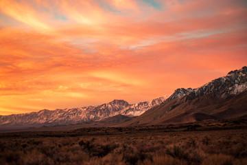Poster Orange Glow first morning sunlight illuminates snowy mountain peaks in California