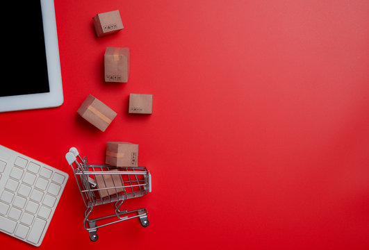 Online shopping,paper boxes,small shopping cart,smartphone and keyboard against red background