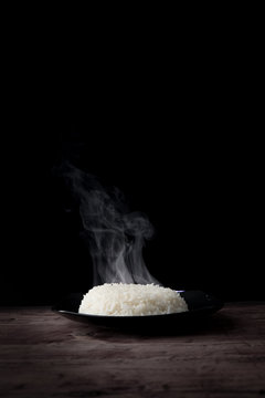 White steam rice with smoke on plate over dark background