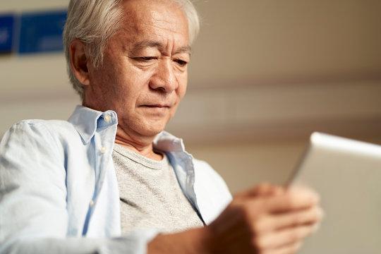 old man looking at digital tablet