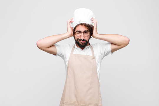 young crazy chef feeling frustrated and annoyed, sick and tired of failure, fed-up with dull, boring tasks against white wall