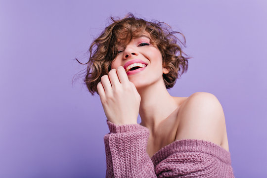 Cheerful white woman with playful smile posing in soft knitted sweater. Indoor portrait of good-looking young lady with short haircut chilling on purple background.