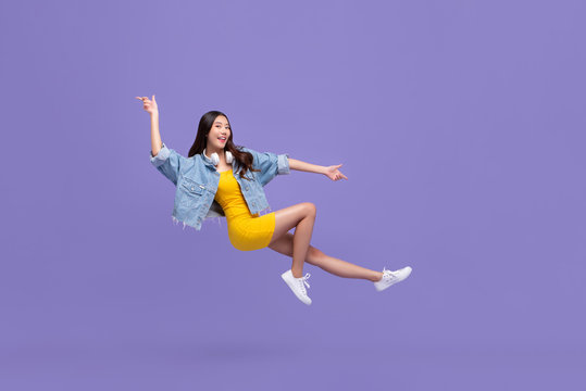 Young beautiful smiling Asian girl floating in mid-air