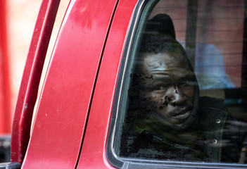 African migrant sits inside a car next to the Old Central Bus Station in Tel Aviv