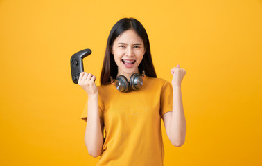 Cheerful beautiful Asian woman in casual yellow t-shirt and playing video games using joysticks...