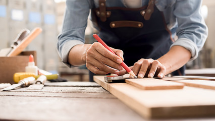 Carpenter working with equipment on wooden table in carpentry shop. woman works in a carpentry shop. Fotomurales