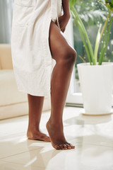 Vertical shot of beautiful legs of unrecognizable Black woman wearing white bathrobe