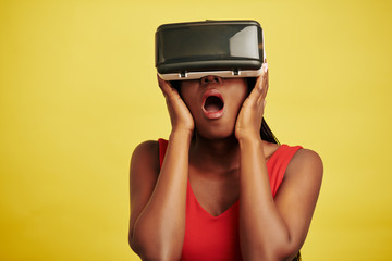 Horizontal studio portrait of Black woman wearing VR headset for first time being impressed, yellow background