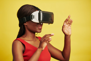 Horizontal studio portrait of Black woman wearing VR headset getting new impressions, yellow background
