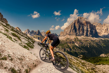 Cycling woman in Dolomites mountains landscape. Girl cycling MTB enduro trail track. Outdoor sport activity.