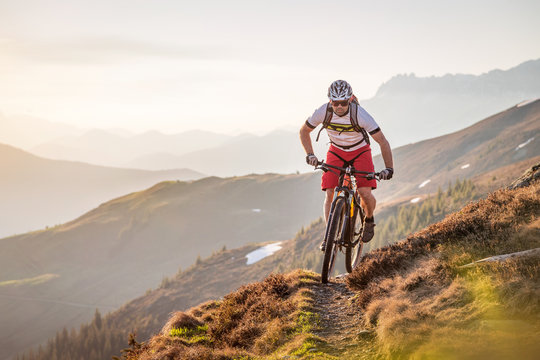 Male mountainbiker riding on a trail in the mountains
