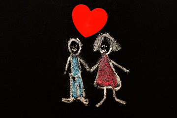 chalk drawing man and woman with red heart on the blackboard.