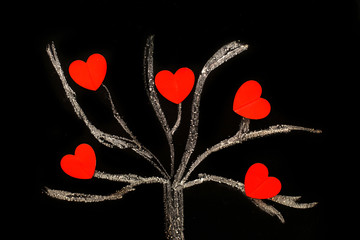 chalk drawing tree on a black chalkboard with red hearts on a tree