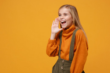 Laughing little kid girl 12-13 years old in turtleneck, jumpsuit isolated on orange yellow...