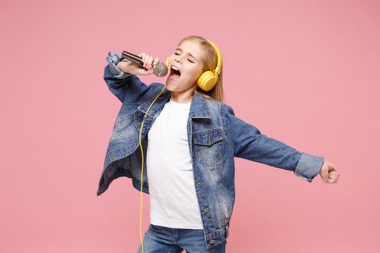 Beautiful little kid girl 12-13 years old in denim jacket isolated on pastel pink background. Childhood lifestyle concept. Mock up copy space. Listen music with headphones sing song in microphone.