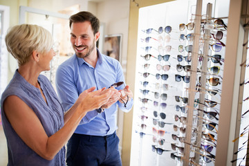 Health care, eyesight and vision concept. Happy mature woman choosing glasses at optics store
