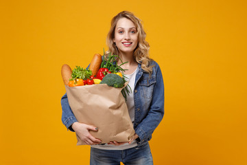 Smiling young woman in denim clothes posing isolated on yellow orange background. Delivery service from shop or restaurant concept. Hold brown craft paper bag for takeaway mock up with food products.