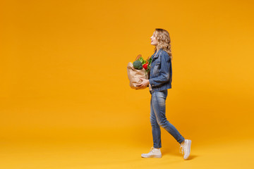 Side view of young woman in denim clothes isolated on yellow orange background. Delivery service...