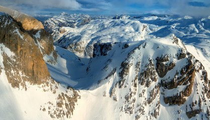 Aerial, panoramic winter view on beautiful Dolomites mountainscape from above. Pale di San Martino mountains range, covered in snow.  Winter mountains theme. San Martino di Castrozza, Italy.
