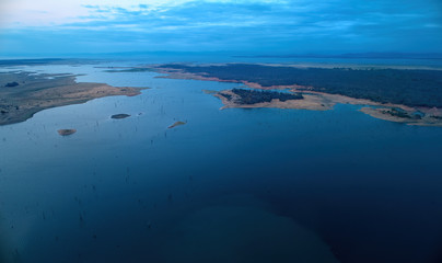 Aerial view of african lake Kariba and surrounding landscape in late evening with setting sun. Blue and pink colors. Dead trees in the water. Zimbabwe. Safari camping on the shore of lake Kariba.