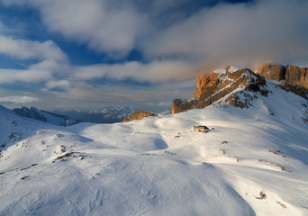Aerial, panoramic winter view on beautiful touristic mountain hut. Dolomites mountainscape from above.  Pale di San Martino mountains range, covered in snow.  Rosetta, San Martino di Castrozza, Italy.