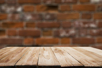 Wooden surface on blurry brick wall background.
