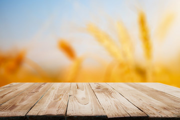 Wooden surface on blurred background of wheat, blue sky, close-up.
