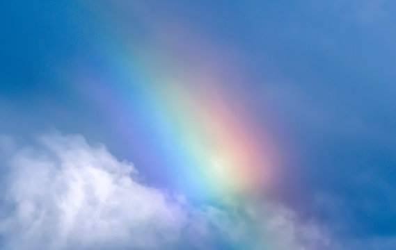 rainbow in blue sky and white clouds