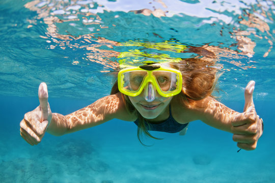 Happy family - active young woman in snorkeling mask dive underwater, see tropical fishes in coral reef sea pool. Travel adventure, swimming activity and watersports on summer beach cruise with kids.