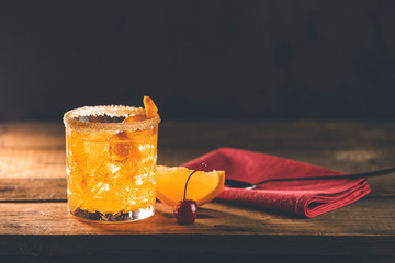 Cocktail Negroni on a old wooden board. Drink with gin, campari martini rosso and orange, an italian cocktail, an aperitif, first mixed in Firenze, Italy, in 1919, alcoholic bitter cocktail
