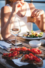 Young woman eating salad, bruschetta with tomato and drinking wine in summer open-air cafe in Italy with sea view background, selective focus. Travel, wanderlust, Italian lifestyle concept