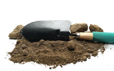 Dirt, soil pile and chunks with gardening trowel, shovel for planting isolated on white background