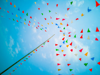 Colorful flags, colorful party decorations, small triangular flags to celebrate the party with the blue sky and clouds as the holiday concept background. Fototapete