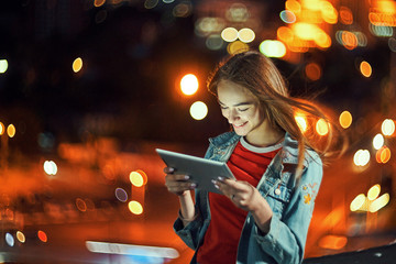 Girl on night cityscape background with street lights, using a digital tablet Fotomurales