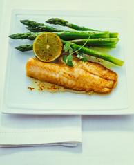 Gebratenes Tilapia Fischfilet mit grünem Spargel auf einer weißen Platte