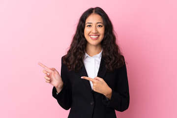 Mixed race business woman over isolated pink background pointing finger to the side