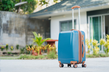 larger plastic suitcase with wheels on the background of a summer house. Rest and travel.