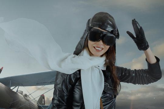 Portrait of lovely brunette girl in retro pilot costume giving military salute