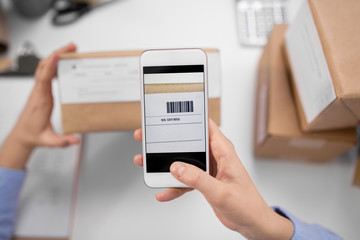 delivery, mail service, people and shipment concept - close up of woman's hands with smartphone scanning barcode on parcel box at post office