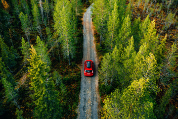 Aerial view of red car with a roof rack on a country road in Finland