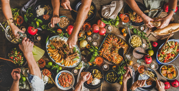 Turkish cuisine family feast. Flat-lay of peoples hands and lamb chops with quince, beans, salad, babaganush, rice pilav, pumpkin dessert, lemonade over rustic table, top view. Middle East cuisine
