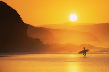 Stores à enrouleur Mer coucher du soleil surfer exiting water at misty sunset