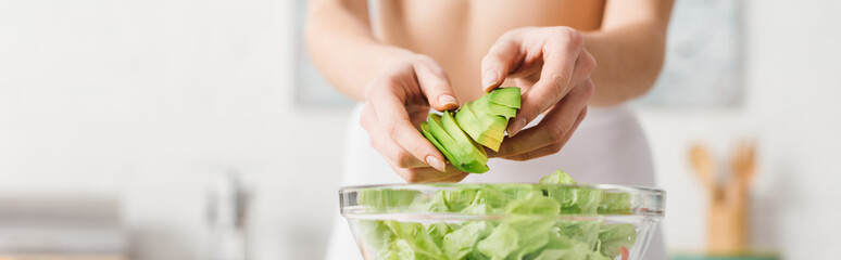 Cropped view of fit woman cooking salad with juicy avocado in kitchen, panoramic shot