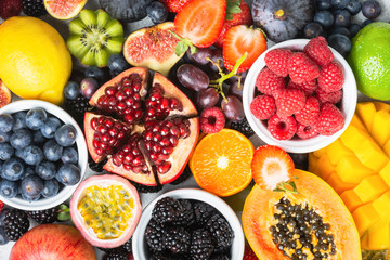 Delicious healthy fruit background mango papaya strawberries oranges passion fruits berries, top view, selective focus
